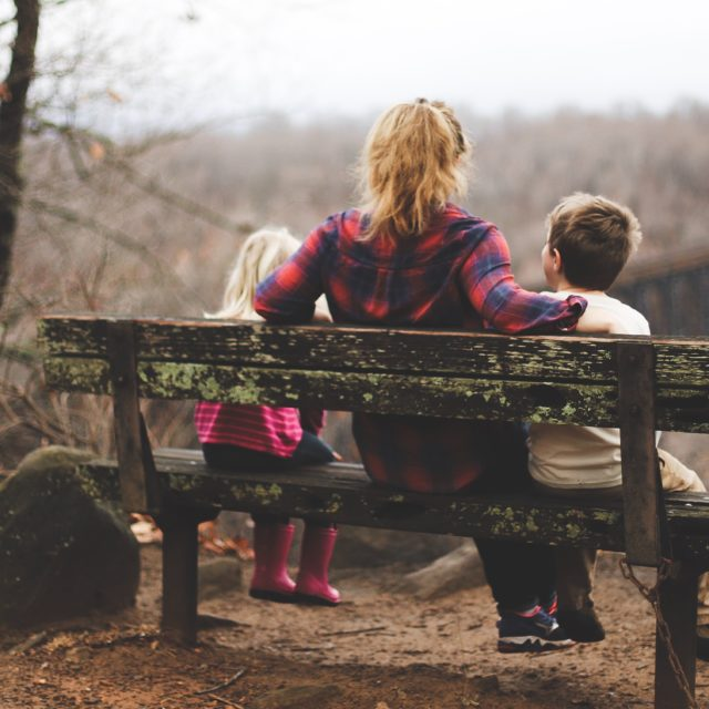 Mother has arm around two children as they stare at forest view