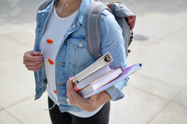 woman in denim jacket holding books