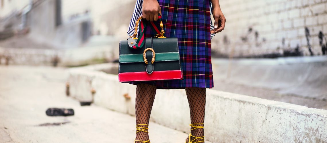 bottom half of model showing detail of stripe bag, tartan skirt, fishnet stockings and yellow heeled sandals