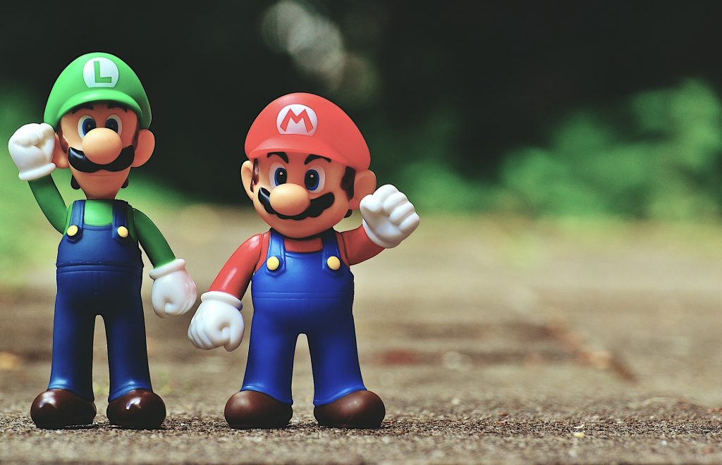 Mario and Luigi figurines with their hands in the air