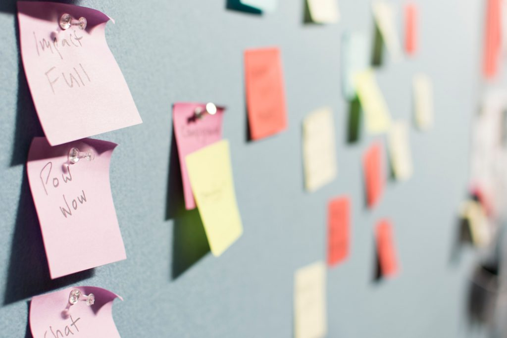 Coloured post-it notes on a mint green wall
